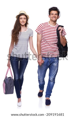 Full length of young happy couple walking with travel bags with joined hands, isolated on white background - stock photo