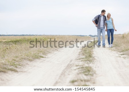 Full length of young hiking couple standing on trail at field - stock photo
