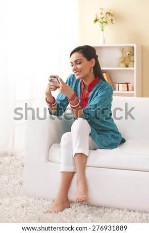Full length of young Indian woman text messaging in living room - stock photo