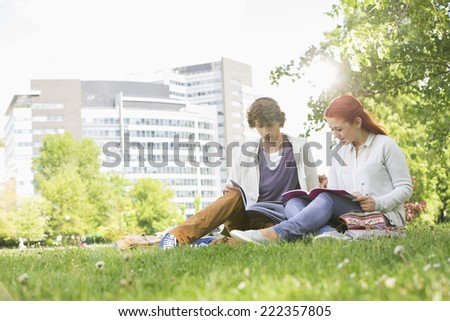 Full length of young male and female friends studying at college campus - stock photo
