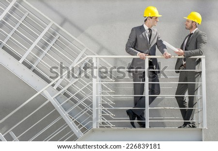 Full length of young male architect discussing on stairway - stock photo