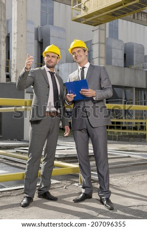 Full length of young male architects with clipboard discussing outside industry - stock photo