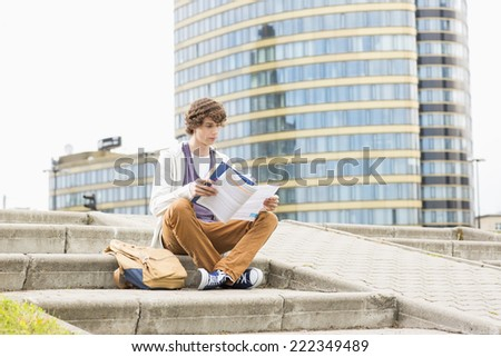 Full length of young male college student reading book against building - stock photo