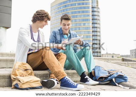 Full length of young male college students studying on steps against building - stock photo