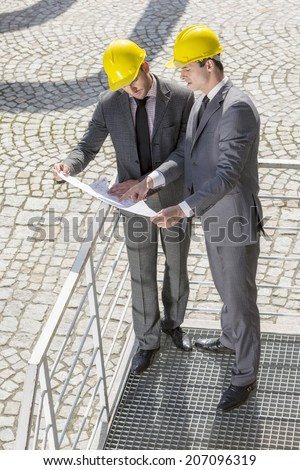 Full length of young male engineers discussing over blueprint on stairway - stock photo
