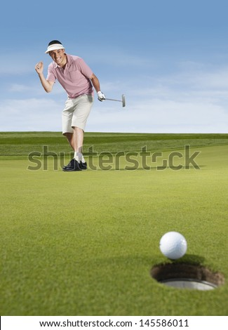 Full length of young male golfer cheering while playing golf - stock photo