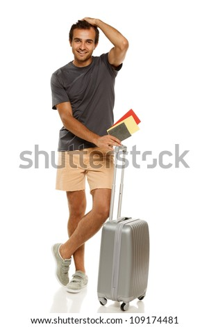 Full length of young male standing with silver suitcase, holding tickets and passport, tidying his hair, isolated on white background - stock photo