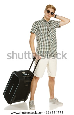Full length of young male tourist standing with suitcase, isolated on white background - stock photo