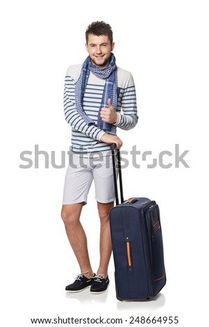 Full length of young male tourist standing with travel suitcase, showing thumb up sign, isolated on white background - stock photo