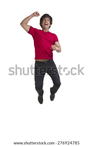 Full length of young man cheering and jumping over white background - stock photo