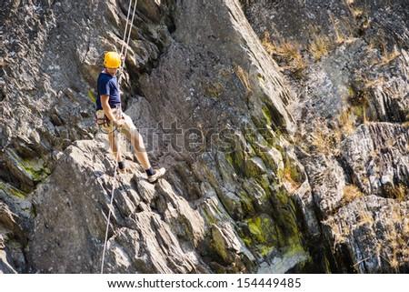 Full length of young man climbing rock - stock photo