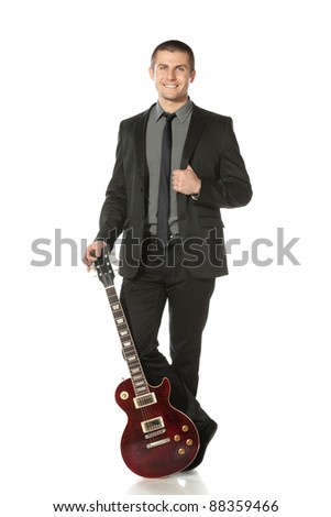 Full length of young man in a suit standing leaning on the guitar over white background - stock photo