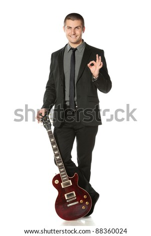 Full length of young man in a suit standing leaning on the guitar showing OK sign over white background - stock photo