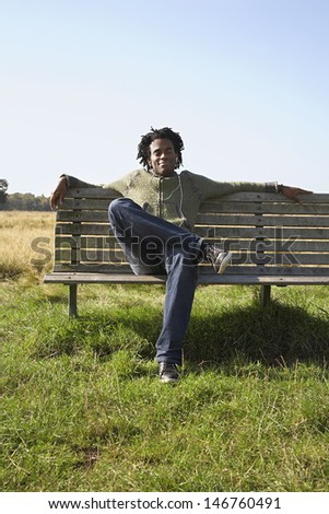 Full length of young man listening to music while sitting on park bench - stock photo