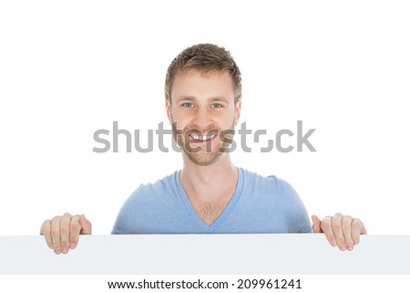 Full length of young man looking at blank billboard isolated on white background - stock photo