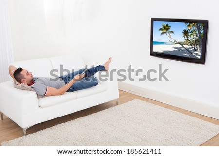 Full length of young man lying on sofa while watching TV at home - stock photo