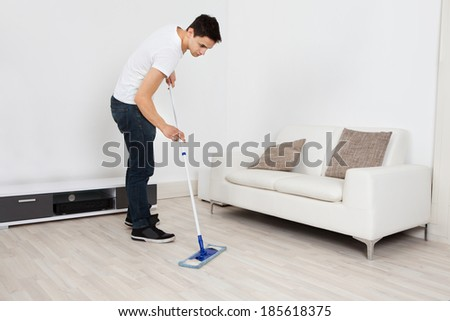 Full length of young man mopping floor at home - stock photo