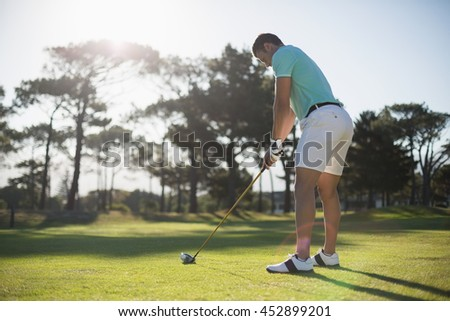 Full length of young man playing golf while standing on field - stock photo