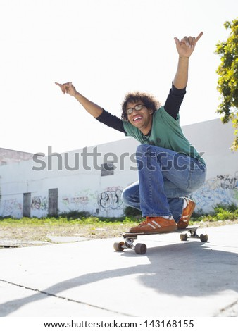 Full length of young man with arms raised on skateboard outdoors - stock photo