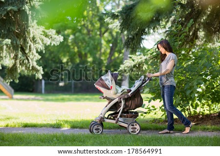 Full length of young mother pushing a stroller in the park - stock photo