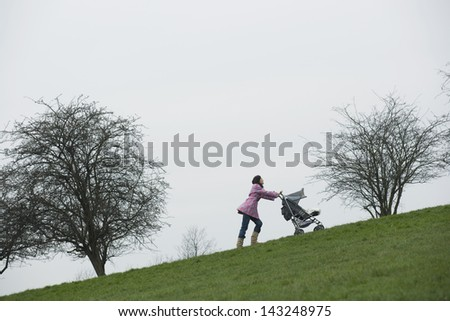 Full length of young mother pushing stroller uphill in park - stock photo