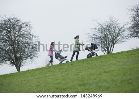 Full length of young mothers pushing baby strollers uphill in park - stock photo