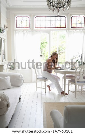 Full length of young pregnant woman using laptop in living room - stock photo