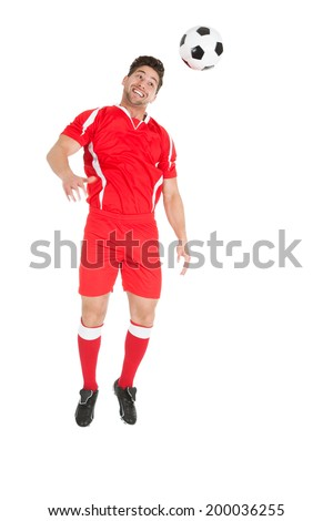 Full length of young soccer player jumping over white background - stock photo