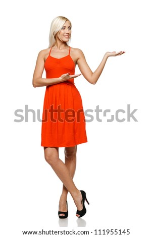 Full length of young trendy woman in bright red dress showing a product - empty copy space on the open hand palm, looking at the copy space on her palm, over white background - stock photo