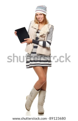 Full length of young winter female holding tablet computer with blank copy space over white background - stock photo