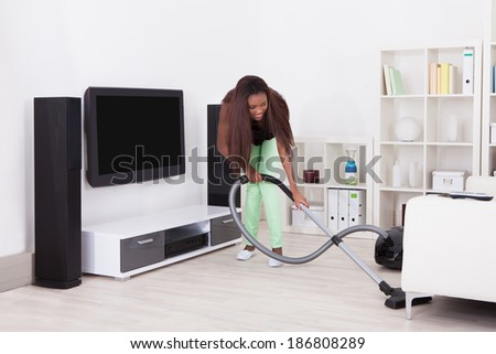 Full length of young woman cleaning home with vacuum cleaner - stock photo