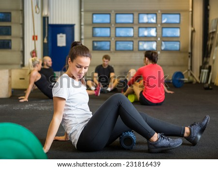 Full length of young woman doing relaxation exercise in crossfit gym - stock photo