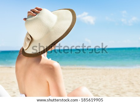 Full length of young woman in bikini enjoying the ocean view while relaxing on beach chair - stock photo