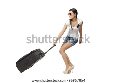 Full length of young woman in casual pulling the heavy travel bag, isolated on white background - stock photo