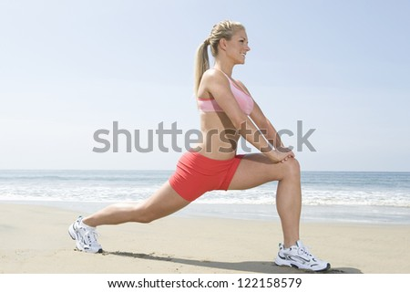Full length of young woman in sportswear doing fitness exercise on beach - stock photo