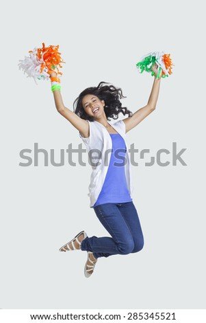 Full length of young woman jumping in mid-air with Indian tricolor pom-poms over colored background - stock photo