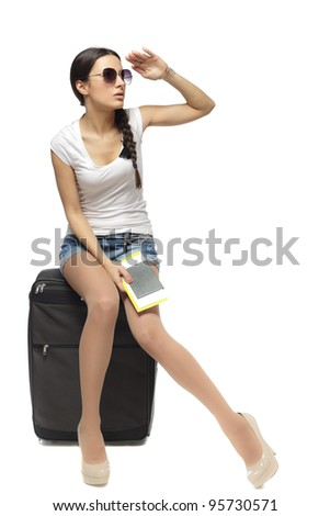 Full length of young woman sitting on her travel bag and holding the tickets with passport looking faraway isolated on white background