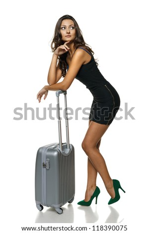 Full length of young woman standing leaning on silver suitcase looking to the side, isolated on white background - stock photo
