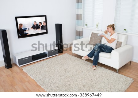 Full length of young woman watching TV while sitting on sofa in living room - stock photo