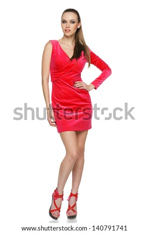 Full length of young woman wearing pink cocktail dress posing with hand on hip against white background - stock photo