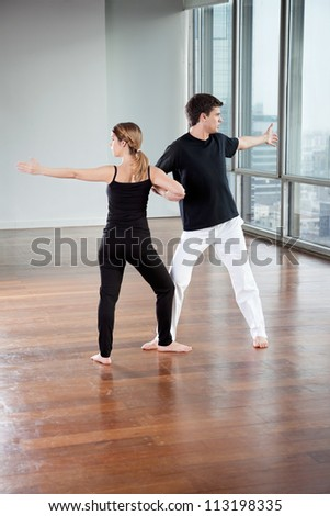 Full length of young yoga partners exercising at gym - stock photo