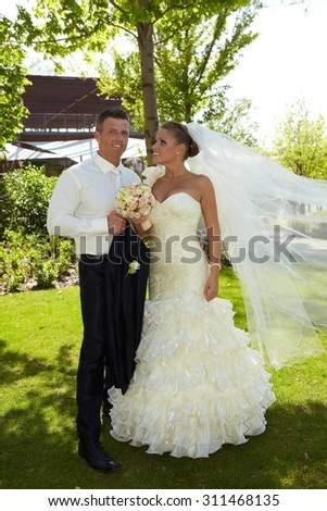 Full-length outdoor photo of happy young couple on wedding-day, embracing. Bride wearing long veil.