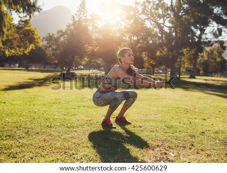 Full length outdoor shot of fit young woman exercising in park. She doing squatting on a sunny morning. - stock photo