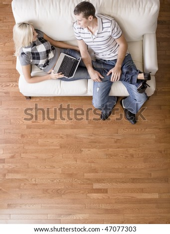 Full length overhead view of couple relaxing together on white couch, with woman using laptop and stretching out with her legs in the man's lap. Vertical format. - stock photo