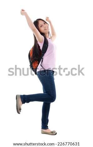 Full length pan Asian teen student cheering with arms raised, isolated on white background. - stock photo
