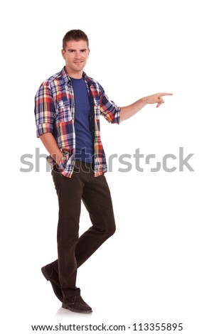 Full length photo of a casual young man pointing towards something and holding one hand in his pocket while looking at the camera. On white background