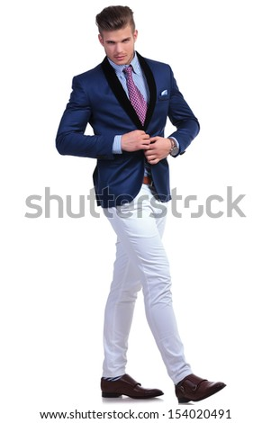 full length photo of a young business man unbuttoning his suit jacket while walking and looking at the camera. on a white background - stock photo