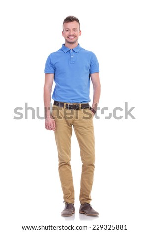 full length photo of a young casual man holding a hand in his pocket while smiling for the camera. isolated on a white background
