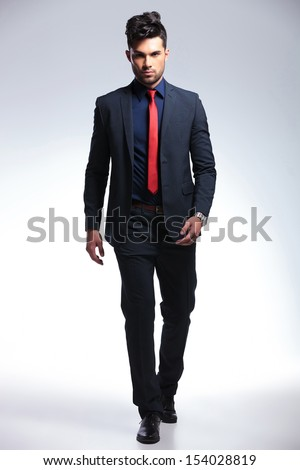full length photo of an elegant young fashion man in tuxedo walking towards the camera. on gray background - stock photo