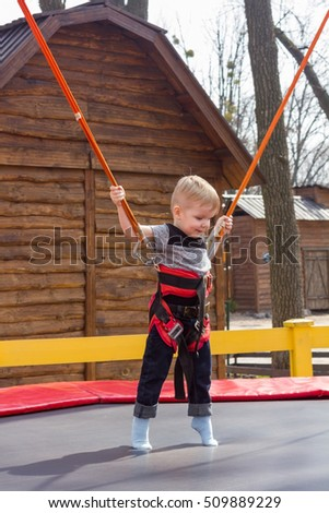 Full-length photo of boy on the trampoline